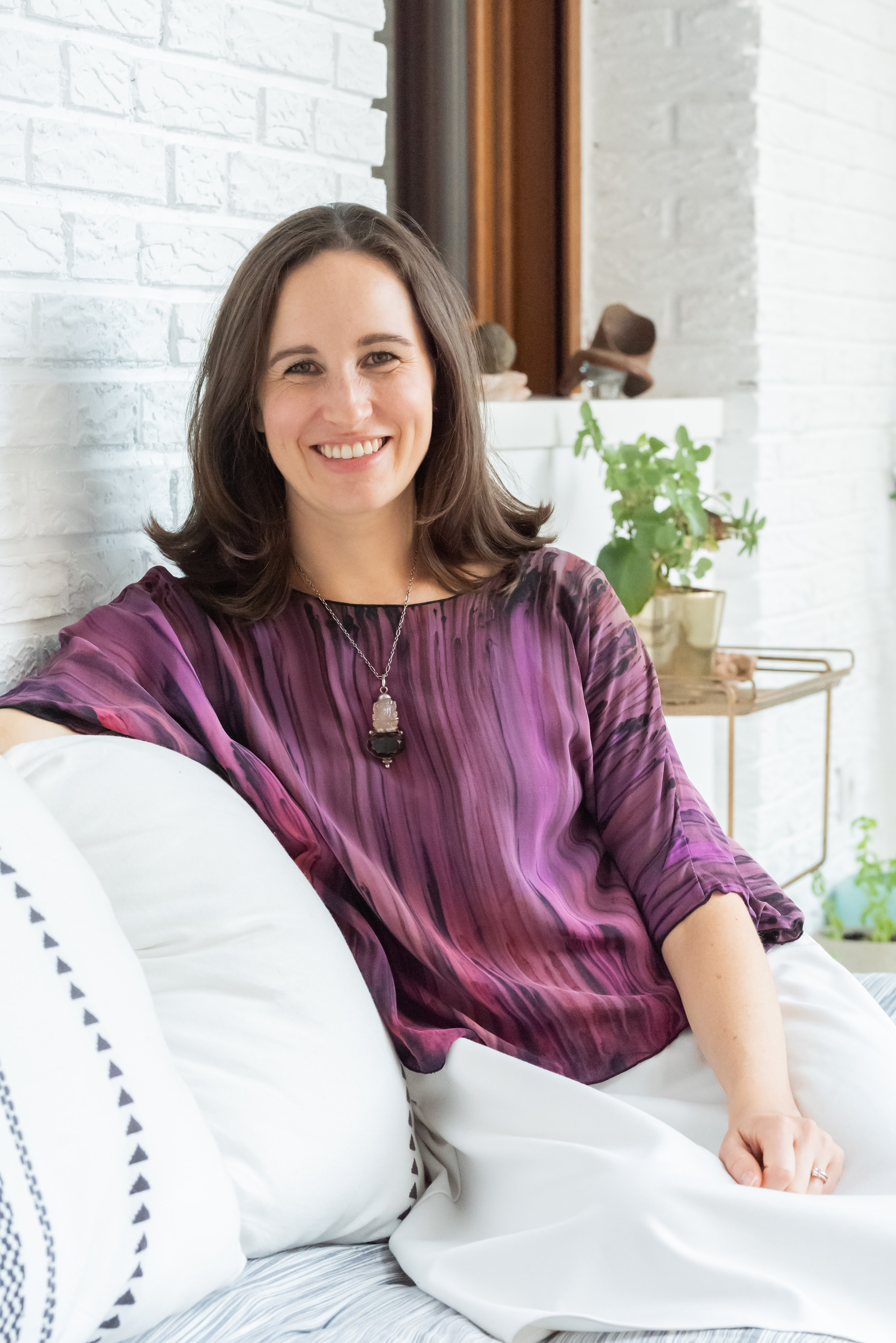 Char Tamason, founder of Health by Intuition, sitting and smiling.